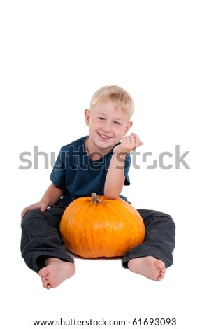 Smilling boy holding a pumpkin in his legs - stock photo