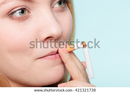 Smilling pretty girl smoking breaked down cigarette. Winning with addicted nicotine problems in young age. Quitting from addiction concept.