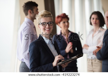 Smilling senior older  business woman with tablet computer  in front her team blured in background. Group of young business people at modern bright  startup office interior. - stock photo