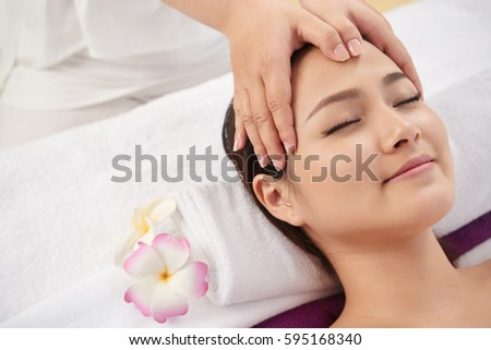 Smilng woman receiving face massage in spa salon