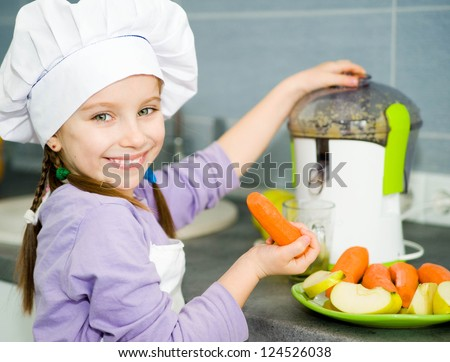 smily cute girl making fresh apple juice with a juice extractor