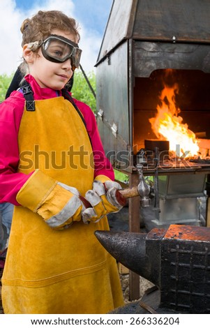 smith girl in goggles and apron with hammer and anvil near the hearth - stock photo