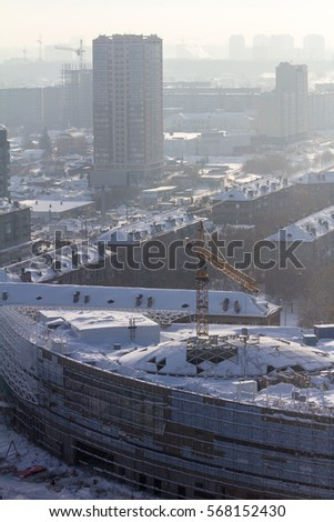 Smoggy winter city. Shopping center under construction.