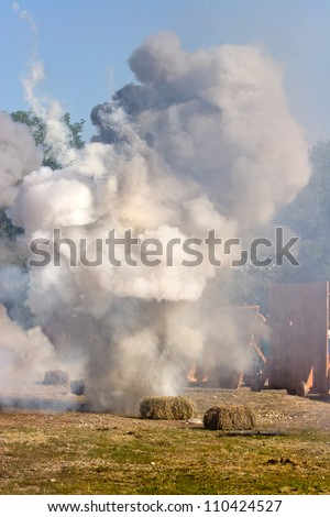 Smoke after explosion on the field with hay