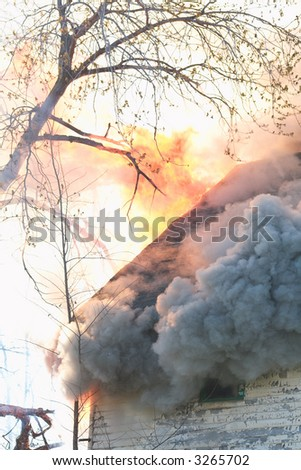 Smoke and flames coming out of the roof of a house - stock photo