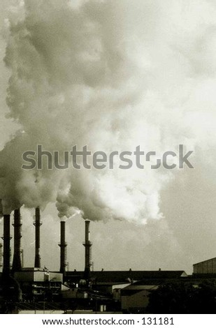 Smoke and steam billowing out from a factory. Vertical, or portrait orientation with sepia toning to enhance gritty, grungy, dirty concept. Copy space in the smoke and steam in upper part of image.