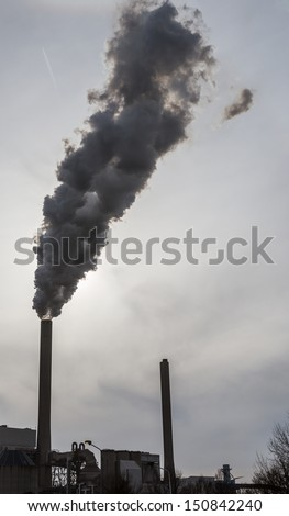 Smoke and steam spew from industrial smoke stackes near Amsterdam in the Netherlands - stock photo