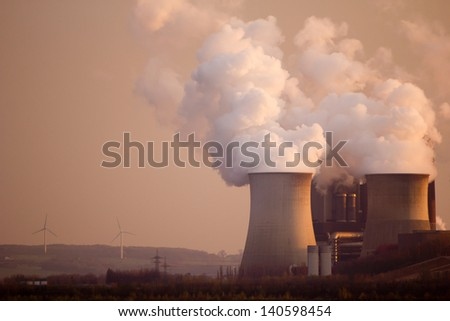 Smoke arising from large cooling towers of a power station - stock photo