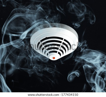 Smoke around fire detector on black background. - stock photo