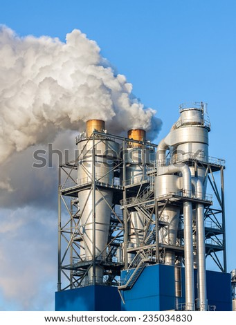 Smoke clouds from a chimney against blue sky. - stock photo