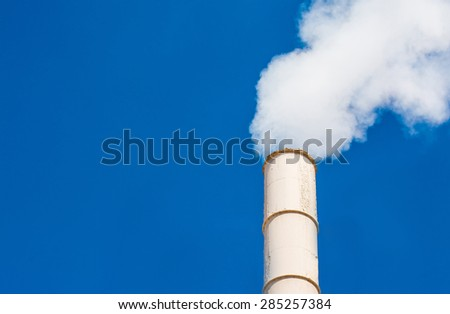 smoke clouds from stack against a clean blue sky