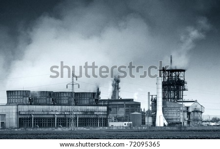 smoke coming out of old factory chimney - noise added for effect - stock photo