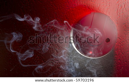 Smoke detector mounted on ceiling with white smoke, red warning light  and space for copy - stock photo