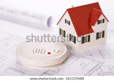 Smoke detector with house and blueprints - stock photo