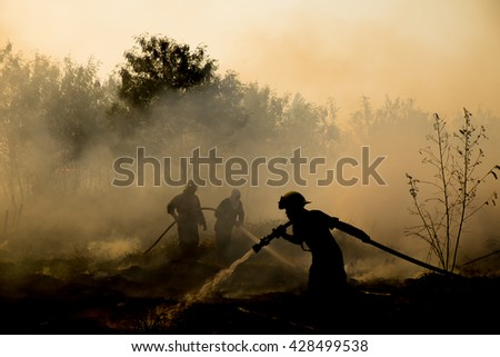 Smoke field and fireman after wildfire sihouette. - stock photo