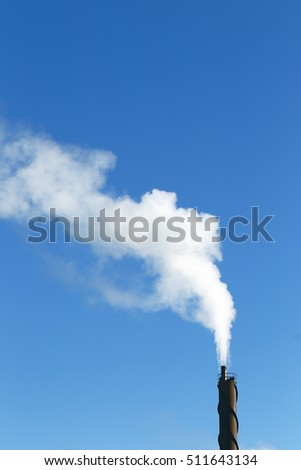Smoke from a chimney on a clear blue sky.