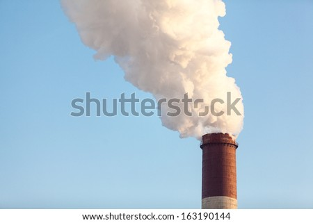 Smoke from a chimney on blue sky background - stock photo