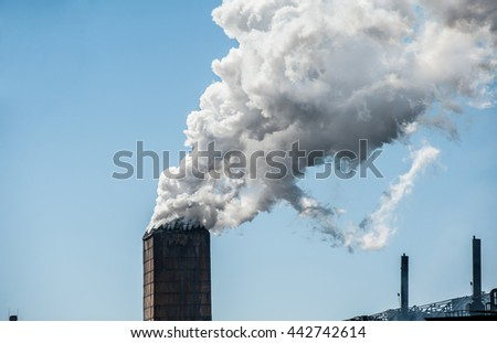 Smoke from a pipe factory polluting air, environmental problems  - stock photo