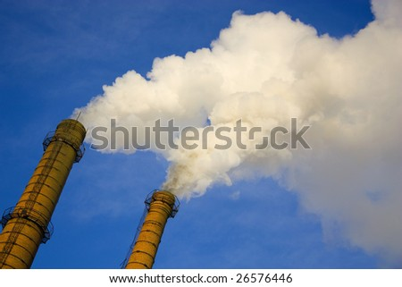 Smoke from a pipe on a background of the light-blue sky.