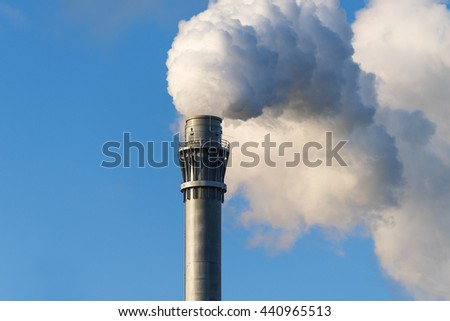 smoke from an industrial chimney against the blue sky with copy space
