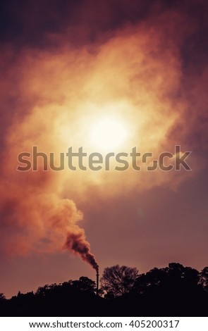 Smoke from an industrial smokestack blocking out the morning sun