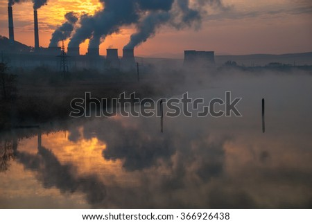 smoke from chimney, Factory pipe polluting air, environmental problems, reflection in water of river, russia, sunset, sun - stock photo