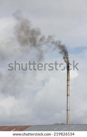 smoke from chimney of rice mill in thailand - stock photo