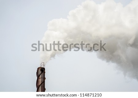 Smoke from metal chimney drifting in the wind - stock photo