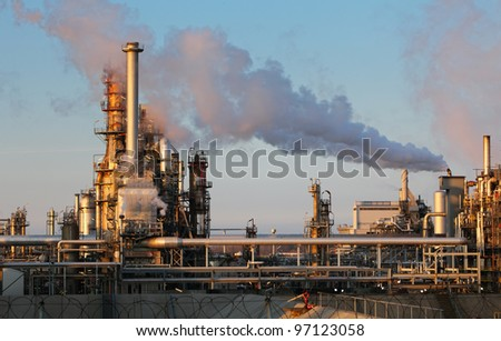 Smoke from the pipes of oil refinery - stock photo