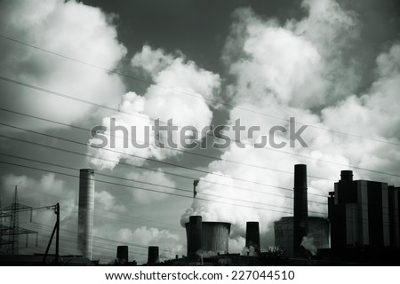 Smoke from the plant rising up to the sky polluting an air. - stock photo