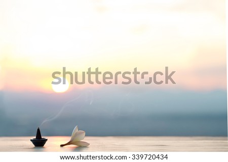 Smoke incense cones with plumeria flower on sunset - stock photo