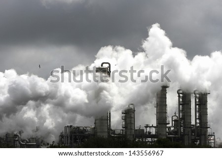 Smoke of heavy industry is highlighted by the sun. Shot in the Dutch industry area of the Europoort