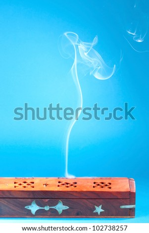 Smoke of Tibetan incense on the blue background