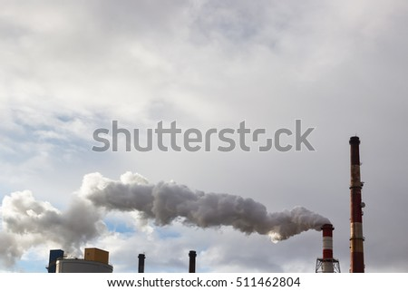 Smoke or steam coming out slowly of tall factory or power plant chimney.