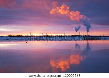 Smoke pipes against colorful sunset at the river - stock photo