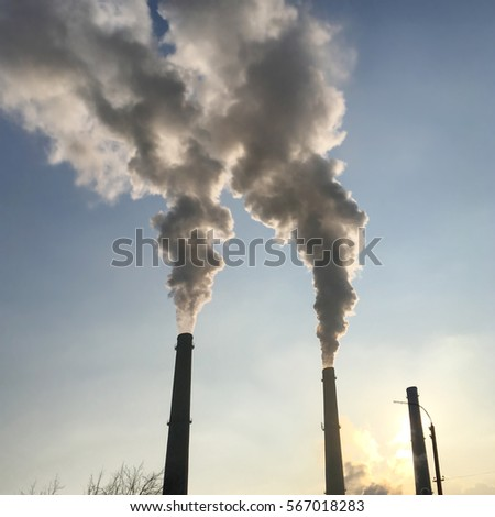 Smoke, pollution from factory industrial pipes against sunset