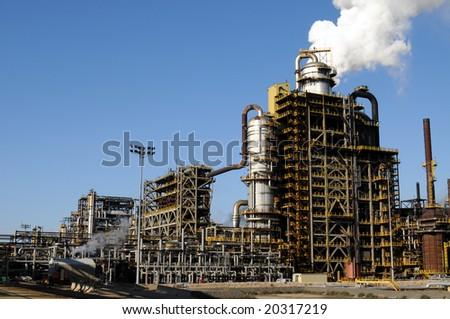 Smoke rising above a petrochemical plant - stock photo