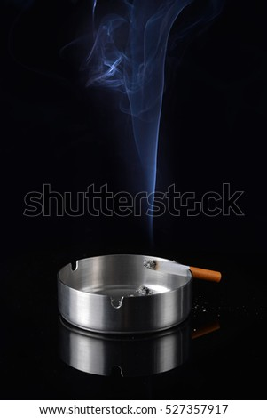 Smoke rising from a cigarette in an ashtray