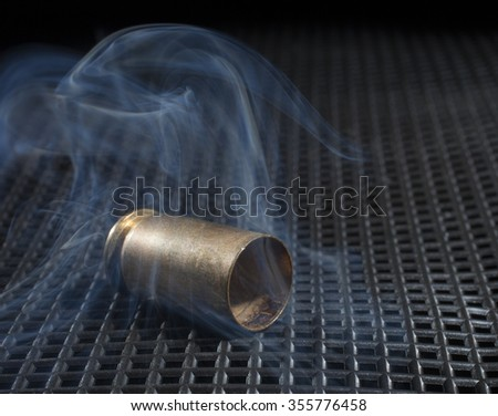 Smoke rising from a pistol bullet that has just been fired - stock photo