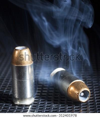 Smoke rising from near a pair of hollow point handgun cartridges - stock photo