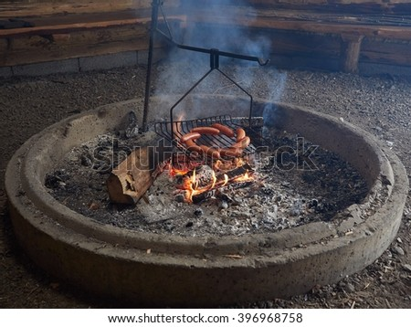 Smoke rising from outdoor fire place in a barbecue hut. Sausages almost ready for eating.