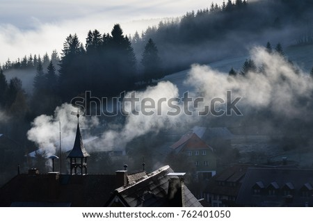 Smoke rising over a village in the Black Forest in the morning