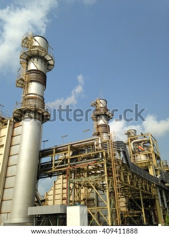 Smoke stack of power generator unit in industrial plant with blue sky