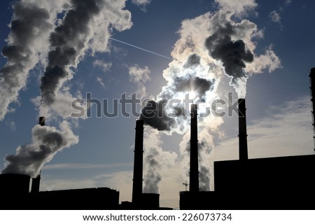 Smoke stacks at coal burning power plant  - stock photo