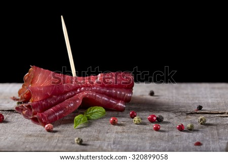 Smoked beef meat slices over rustic background - stock photo