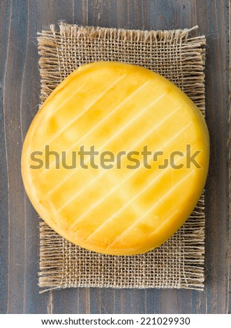 Smoked cheese wheel, tomatoes and bread on wooden table - stock photo