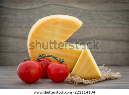 Smoked cheese wheel, tomatoes on wooden table - stock photo
