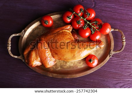 Smoked chicken leg with cherry tomatoes on metal tray on color wooden table background - stock photo