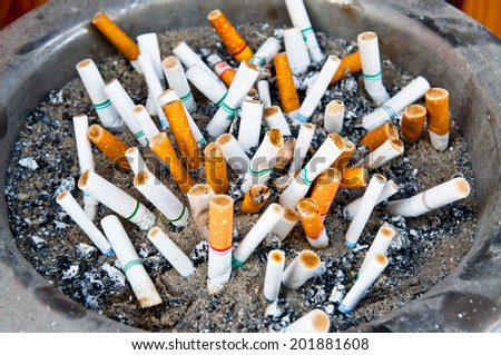 Smoked Cigarettes Butts in a Dirty Ashtray Big Bin. Life concept Photo. - stock photo