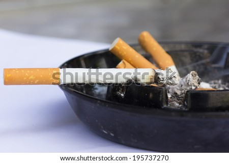 smoked cigarettes in a dirty ashtray - stock photo